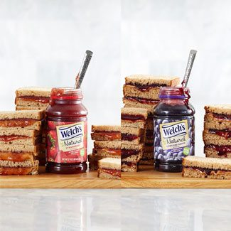 Two jars or Welch's Natural Strawberry and Grape Spead surrounded by stacks of peanut butter and jelly.