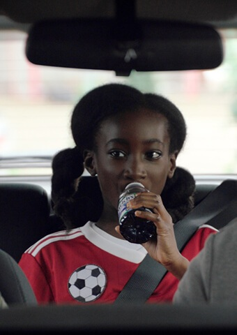 Daughter sitting in the backseat drinking Welch's grape juice on the way to soccer practice.