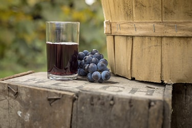 Close up of a glass of Welch's grape juice next to a basket of grapes