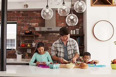 Dad cooking with his kids in the kitchen