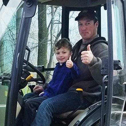 Tracy Beckman and his son giving a thumbs up while driving a tractor.