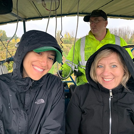 Two Welch's staff members touring a vineyard, smiling.