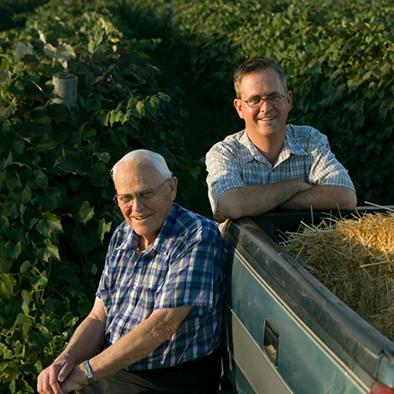 Son and Father on their farm standing at their truck