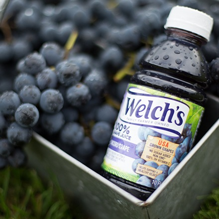 Bottle of Welch's 100% Grape Juice in a basket of Concord grapes.