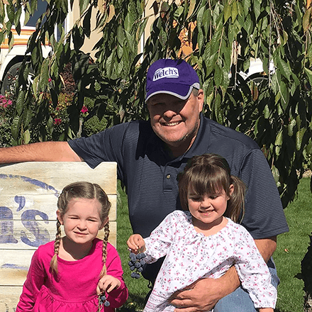 Tim Grow, Welch's Farmer, and his two granddaughters on their farm.