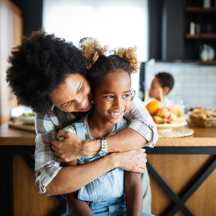 Mom hugging her daughter from behind, both smiling in the kitchen.