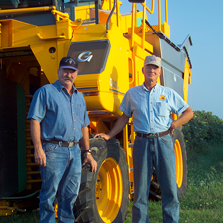 Two farm workers standing next to tractor