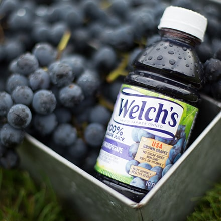 Bottle of Welch's 100% Grape Juice in a basket of grapes