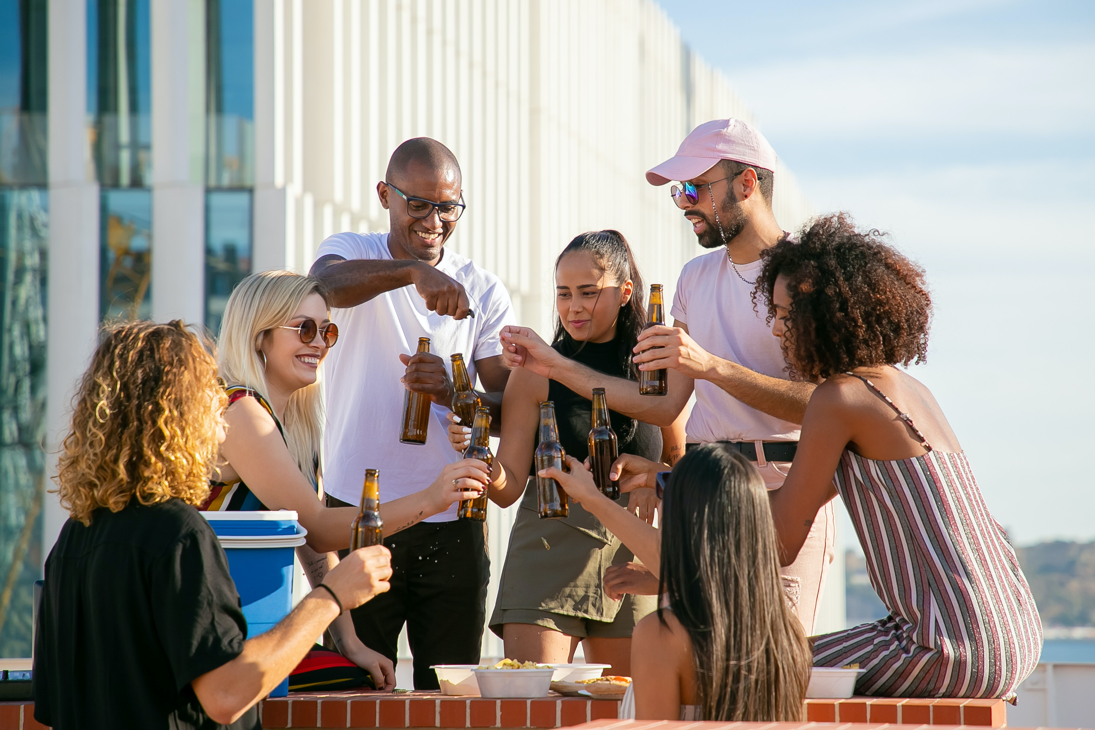 People standing together and holding glass bottles on a rooftop