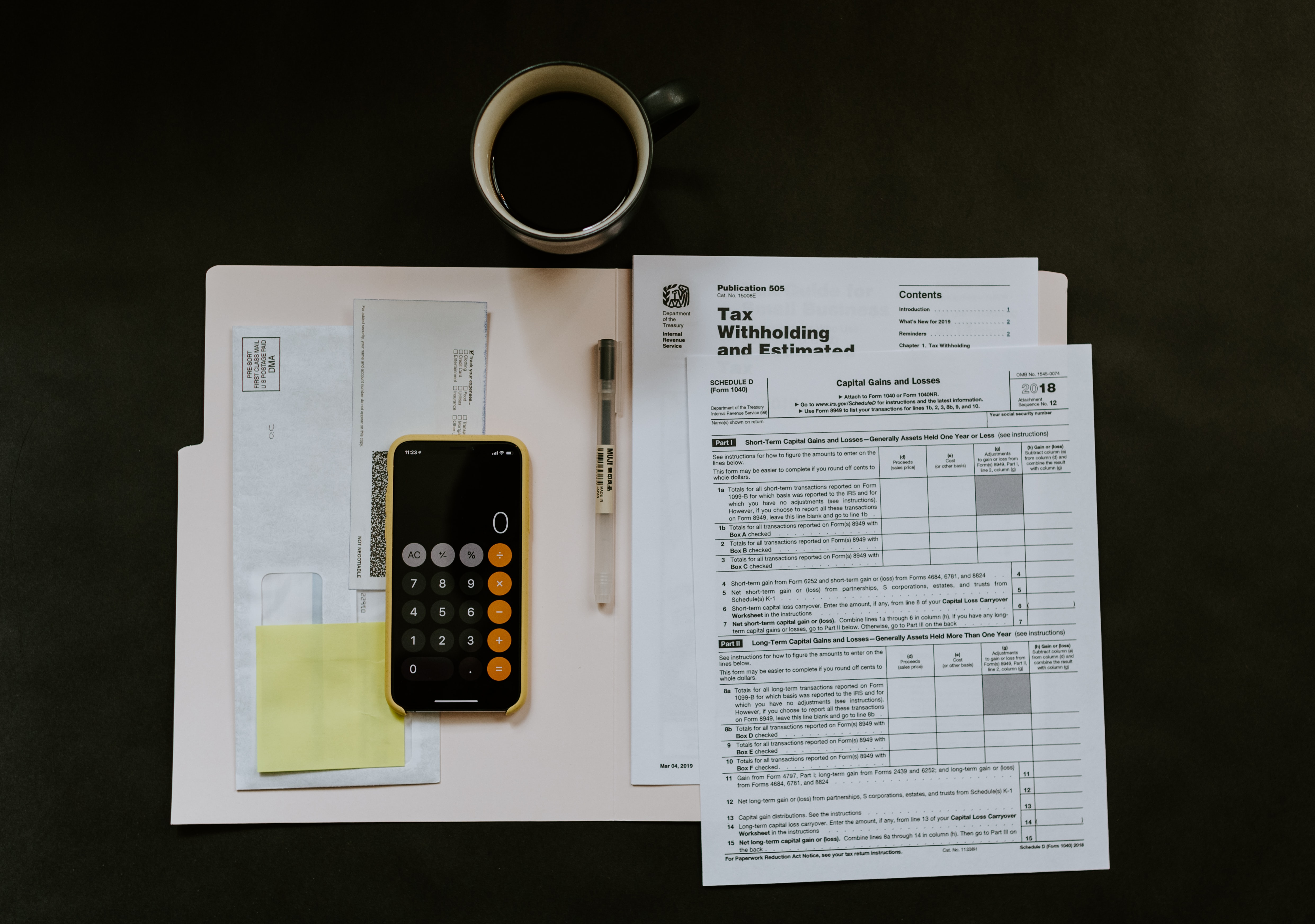 Calculator, tax return forms, pen, envelopes, yellow sticky note and roll of tape