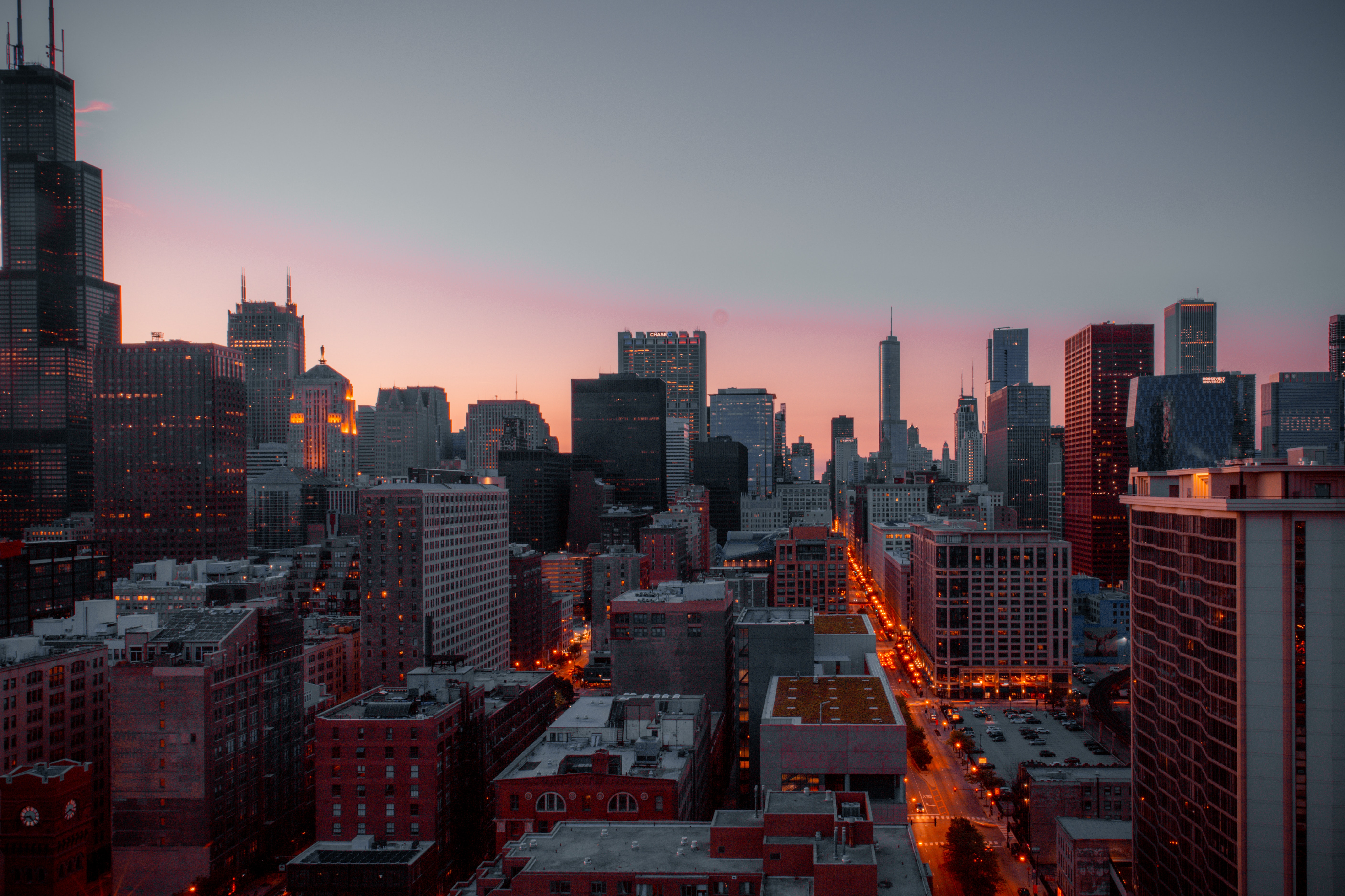 City skyline overlooking rooftops during orange sunset