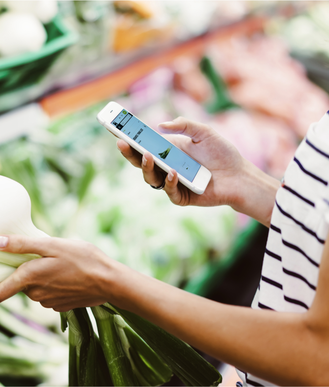 Photo of a woman holding her phone looking at the Ahold Delhaize app and holding large spring onions