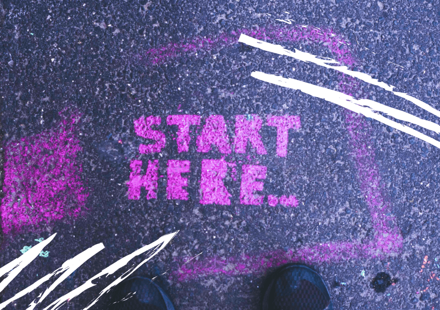 A photo of the words 'Start here' painted onto the street