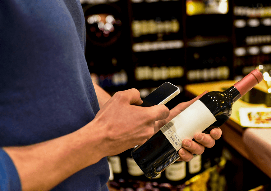 A man's hands holding a bottle of wine and a phone, which he is using to scan the bottle whilst shopping