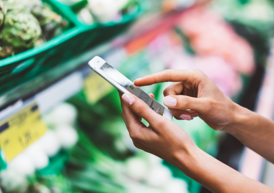 A woman's hands holding a phone and interacting with the Ahold Delhaize retail app in a supermarket