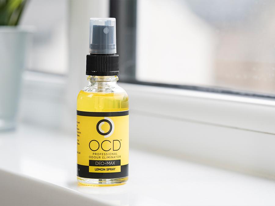 yellow ocd odour neutraliser spray bottle, full of yellow liquid, sat next to a plant on a window