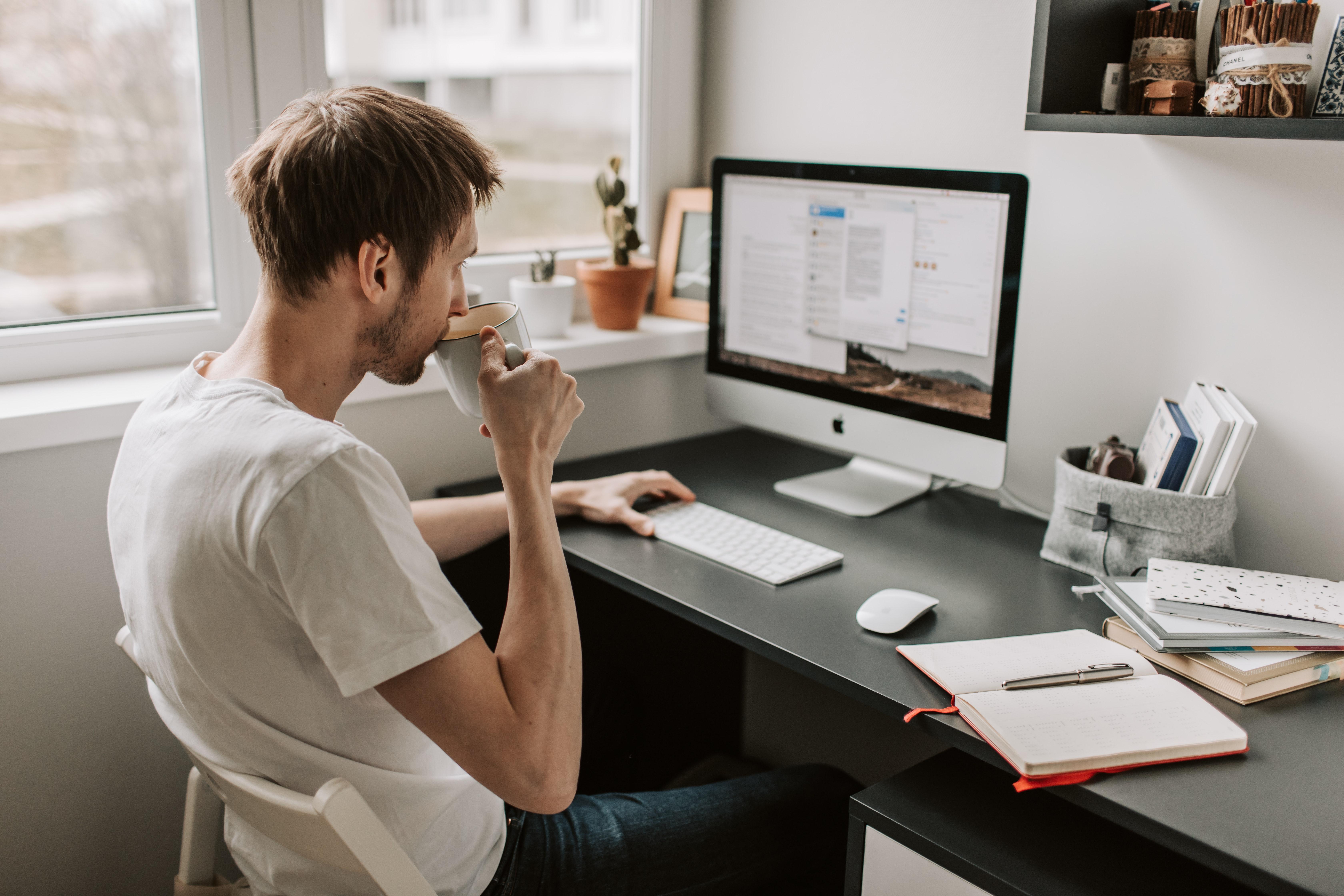 Homme buvant son café devant son ordinateur