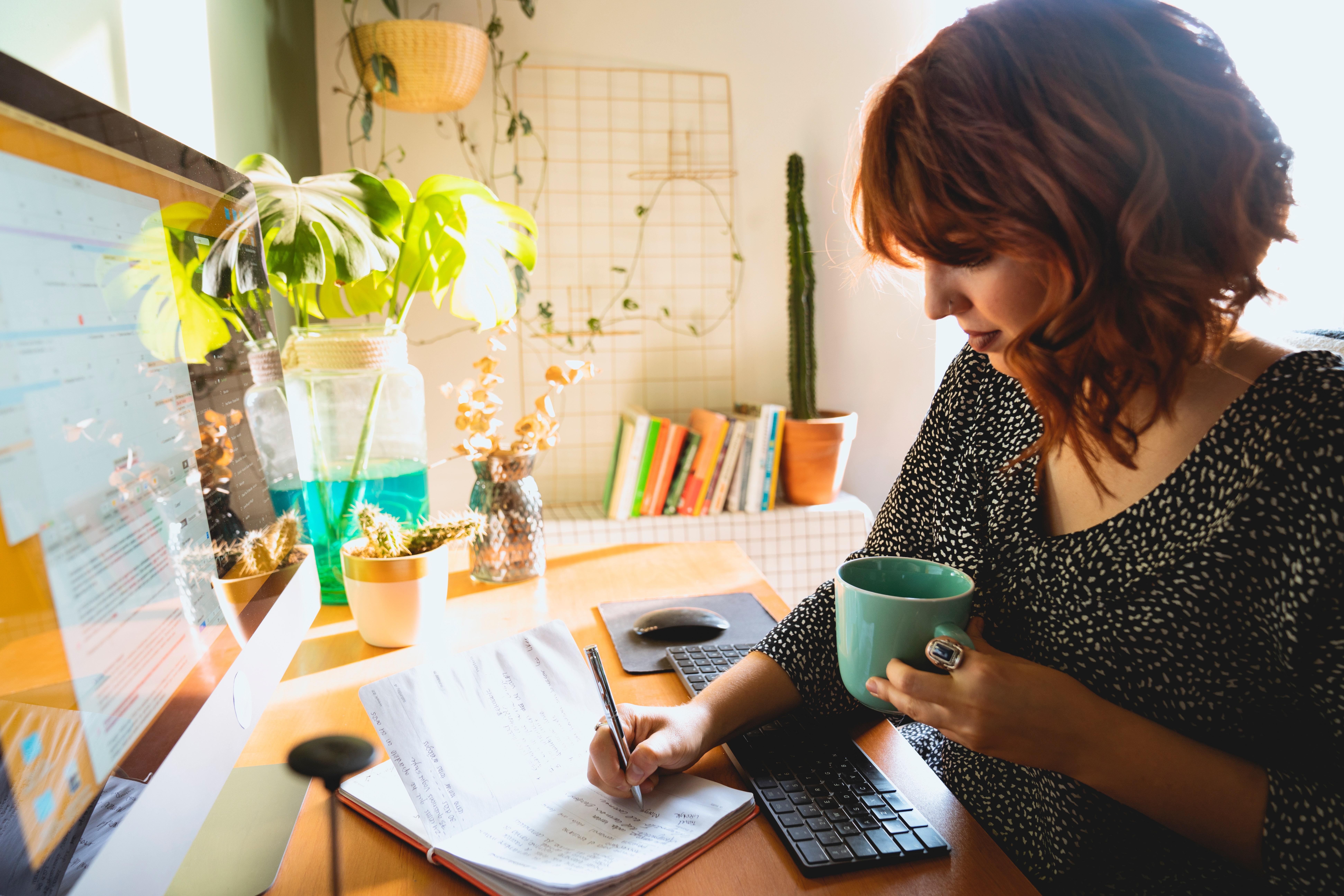 Femme prenant des notes sur un carnet devant son ordinateur